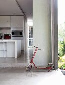 Child's scooter in open doorway leading to kitchen with island counter