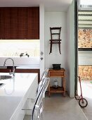 Modern kitchen with contrasting decor, old bistro chair hung on wall & wooden side table