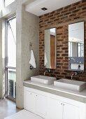 Twin basins on washstand below mirrors on brick wall