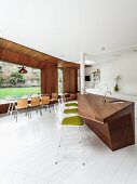 Kitchen counter in exotic wood and Bauhaus-style bar stools; large windows in background with long glass table and pale wooden chairs