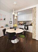 Offener Wohraum mit weisser Küchenzeile und verschiebbarer Trennwand mit großem Muster; im Vordergrund eine Essgruppe in Schwarz und Weiss