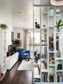 Raumhohes Bücherregal als Raumteiler mit Blick auf blauen Ledersessel vor offener Balkontür