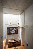 Arbeitsplatz mit geschwungenem Holzschreibtisch zwischen Betonwänden; über dem Schreibtisch ein modernes Gemälde