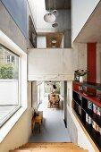 Offener Wohnraum im Beton Stil mit mehreren Ebenen; im Vordergrund führt eine Holztreppe aus hellem Holz zum Essbereich