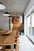 Rustikaler Esstisch mit Stühlen vor raumhoher Glasfront; von der Betondecke hängen drei schlichte Metalllampenschirme