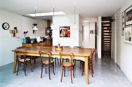 Esszimmer mit Betonestrich, langer Esstafel und Holzstühlen mit geschwungener Lehne