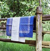 Blue and white table linen hanging over wooden fence