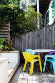Colourful, designer plastic chairs on sheltered wooden terrace