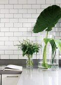 Grüne Blätter in Glasgefässen vor ziegelartig gefliester Rückwand auf Küchenarbeitsfläche
