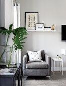 Sitzplatz am Fenster mit schlichtem, grauem Designersessel unter Wandbord mit Kunstsammlung