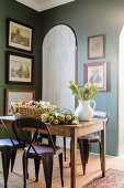 Flowers on rustic wooden table and retro-style metal chairs in corner of traditional dining room with framed pictures on green walls
