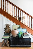 Antiquarian books on black, wooden trunk and footstool in front of staircase with wooden balustrade