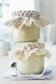 Jars of rice pudding topped with crocheted doilies for presents