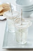 Lacy paper doilies pierced by straws on drinking glasses: as decoration and to keep out insects