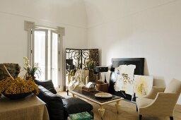 Schwarzes Sofa und heller Sessel um Couchtisch in minimalistischem Wohnraum mit postmodernem Flair