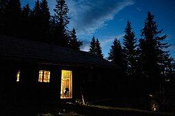 Beleuchtete Almhütte mit offener Tür am Abend
