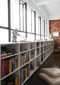 Halbhohes Bücherregal unterhalb der gesamten Fensterband-Breite