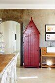 Rotbraun gestrichenes ehemaliges Wachhäuschen an Wand mit Betonlook in Esszimmer neben Rundbogendurchgang