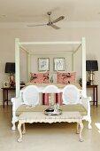 Vintage Couchtisch und Sitzbank im Rokoko-Stil vor Himmelbett in traditionellem Ambiente