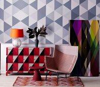 Farbgestaltung mit geometrischen Dreiecks-Mustern auf Wand, Schrank und Kommode, davor Sessel und Beistelltisch