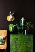 Hirschköpfe aus weisser Keramik mit farbigen Grundtafeln auf schwarzer Wand und Kommode im Dschungel-Look mit grüner Pferdefigur