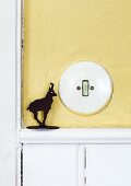 Old Bakelite light switch on wall painted pale yellow and small ibex figurine on dado rail