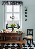 Vegetables on Biedermeier table, old hunting horn and collection of small hunting trophies in kitchen-dining room; seat of chair upholstered with old flour sack