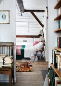 Attic guest room with white clapboard walls, many books and board chair used as bedside table
