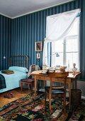 Blue striped wallpaper and Biedermeier desk below window in guest room with single bed