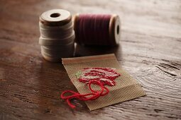 Embroidery sample and reels of yarn on rustic wooden surface