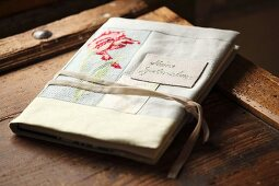 Book with hand-crafted, embroidered book jacket on wooden surface
