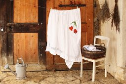 Table cloth with embroidered floral motif hanging over washing line and laundry basket on chair in rustic interior