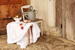Table cloth embroidered with floral motif on wooden trestle in front of watering can on kitchen chair in rustic interior