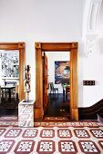 Sculpture on pedestal between doorways with profiled wooden frames and patterned tiled floor in foyer