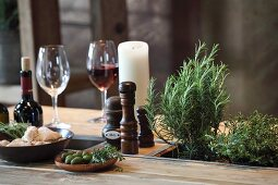 Rustic dining table made from pallet with potted herbs, candles and wine glasses