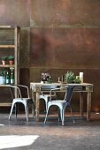 Rustic dining table made from pallet, metal chairs and partially visible shelving against corten steel wall