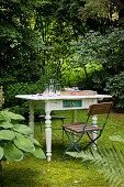 Folding garden chair and white-painted, shabby-chic table with turned legs in garden
