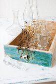 Old stemware in vintage drawer with front painted blue-green; collection of glass carafes in background
