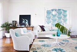 Weisse Rattansessel und Sofa um weissen Tisch im Wohnzimmer; gemusterte Tapete und Teppich in Türkis