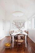 Weisser Tisch und Thonetstühle auf edlem Dielenboden in weissem, minimalistischem Esszimmer