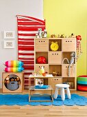 Wooden shelves with storage boxes as organiser in colourful child's bedroom
