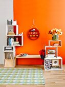 Stacked, cubic shelving modules & round ornamental shelving on wall above cloakroom bench against orange wall