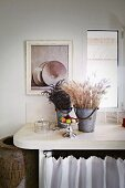 Dried flowers in metal buckets on worksurface with rounded corners below window
