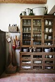Old kitchen cupboard with glass-fronted upper section and terracotta floor in rustic ambiance