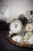 Collection of vintage clocks on mirror with carved frame
