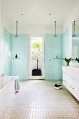 Spacious bathroom with bathtub and washstand; shower area with two rainfall showers behind glass partition and door leading to balcony