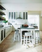 Island counter and stools in modern, white fitted kitchen with tiled floor