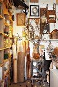 Sammelsurium aus Stoffrollen, Bildern an der Wand und Zweigen in Vase vor Regal