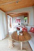 Rustikaler Holztisch und weisses Sofa auf überdachter Terrasse mit weissen, bodenlangen Vorhängen; Blick durch offene Tür ins Esszimmer