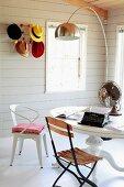 Verschiedene Stühle vor rundem Tisch unter Bogenlampe; an Wand Bauhaus Garderobe mit farbigen Hüten
